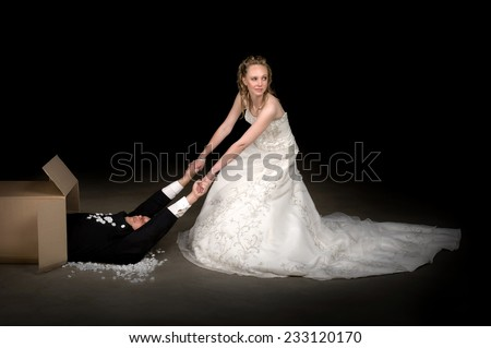 Bride getting a brand new husband out of a box - stock photo