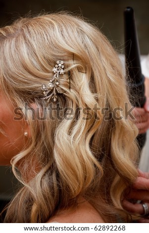Bride getting hair styled - stock photo