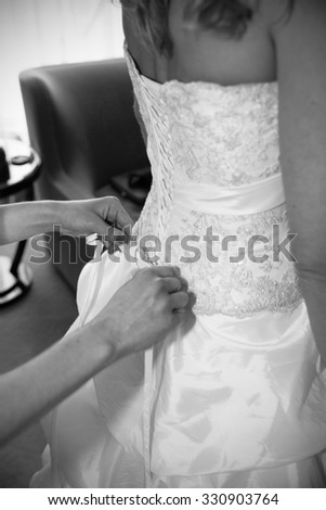 Bride getting her wedding dress tied up. - stock photo