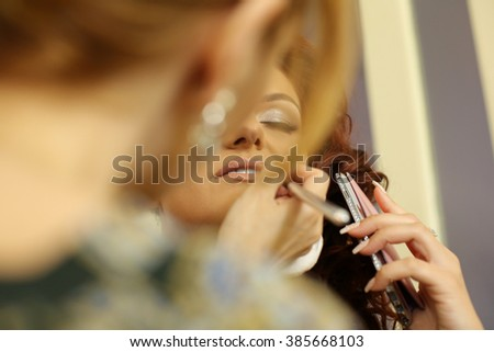 Bride getting professional makeup for wedding day