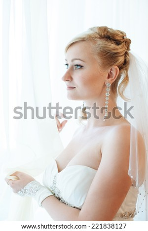 Bride getting ready. beautiful bride in white wedding dress with hairstyle and bright makeup. Happy sexy girl waiting for groom. Romantic lady in bridal dress have final preparation for wedding.
