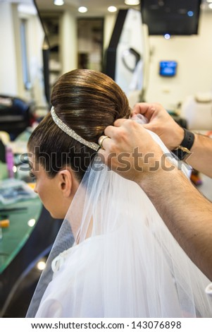 bride getting ready for wedding in hair dressing saloon - stock photo