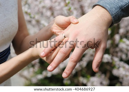 Bride gives an engagement ring to her groom. Wedding and honeymoon concept. wedding day. focus on hand and ring. Blossoming bushes on background. outdoors.