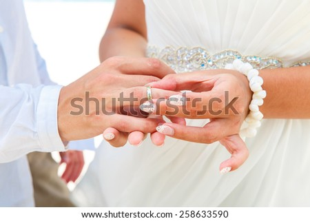Bride giving an engagement ring to her groom under the arch decorated with flowers on the sandy beach. Wedding ceremony on a tropical beach in blue. Wedding and honeymoon concept. - stock photo