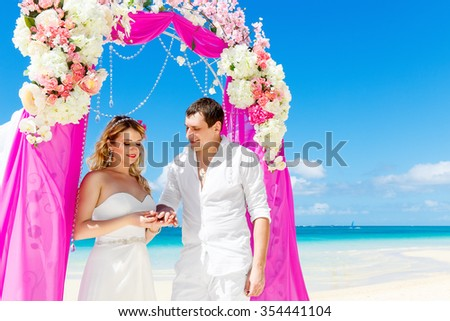 Bride giving an engagement ring to his groom under the arch decorated with flowers on the sandy beach. Wedding ceremony on a tropical beach purple. Wedding and honeymoon concept.