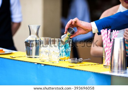 Bride & groom couple mixing alcohol cocktails at wedding reception - stock photo