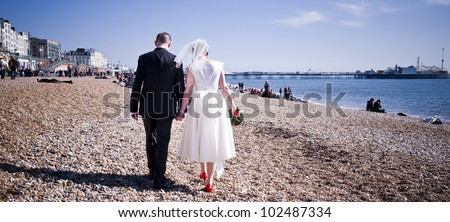 Bride & Groom holding hands on the seafront - stock photo