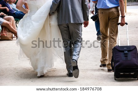 Bride, groom, photograph and suitcase with rose bouquet. Before a wedding. Taking a new road in life idea. - stock photo