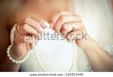 Bride hands putting on pearls