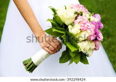 Bride hands with wedding ring holding bridal bouquet