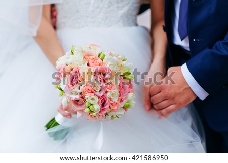 Bride hold groom by the hand and wedding bouquet. Focus on wedding flower bouquet. Crop by chest and legs. Bride in wedding dress, groom wears classic clothes.