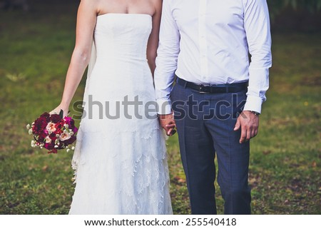 Bride hold groom by the hand and wedding bouquet. Wedding flower bouquet in bride's hand. Crop by chest and legs. Bride in wedding dress, groom wears classic clothes. Vintage style coloring - stock photo