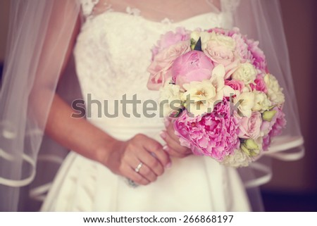 Bride holding a beautiful peonies bouquet