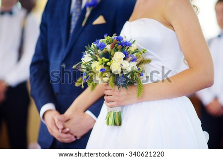 Bride holding a beautiful wedding bouquet on wedding day - stock photo