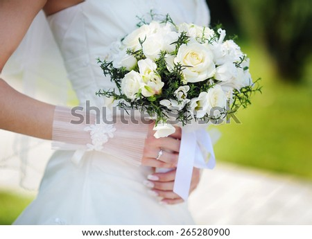 Bride holding a beautiful white wedding bouquet. - stock photo