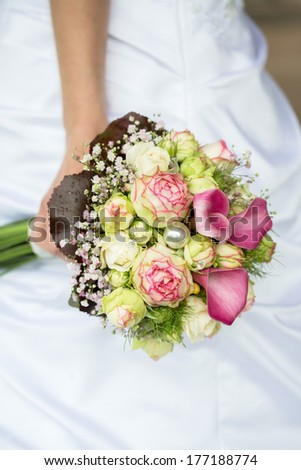 Bride holding a bouquet of purple callas - stock photo
