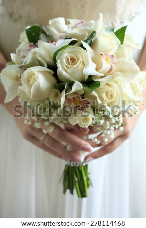 Bride holding a delicate bouquet of roses and orchid in pastel colours on holiday background, vertical picture