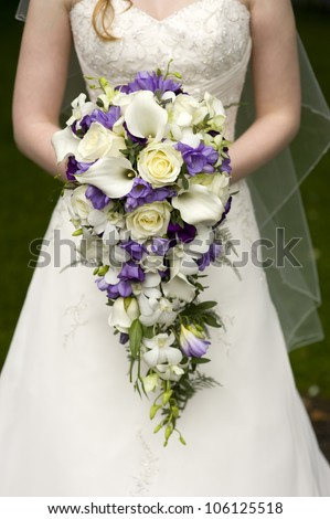 bride holding a large teardrop wedding bouquet - stock photo