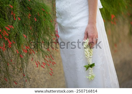 Bride holding a Thai wedding garland. - stock photo