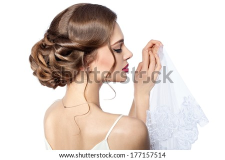 Bride holding a veil with a beautiful hairdo. - stock photo