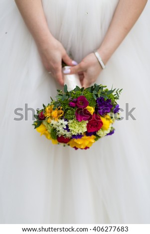 Bride holding a wedding bouquet against a white dress background