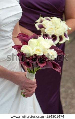 bride holding a wedding bouquet of purple plus white roses and calla lilies - stock photo