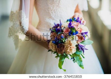 bride holding a wedding bouquet with blue flowers - stock photo