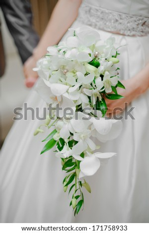 bride holding a white wedding bouquet in her arms