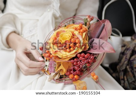 Bride holding beautiful orange wedding flowers bouquet  - stock photo