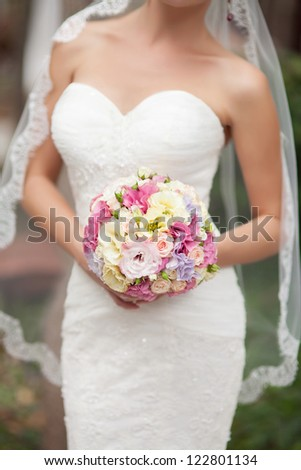 Bride holding beautiful wedding bouquet of purple, pink, yellow and white flowers. Slim newlywed woman with fresh flowers at her wedding day/ waiting for groom outdoors. - stock photo
