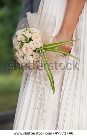 Bride holding bouquet of flowers, outdoor shot