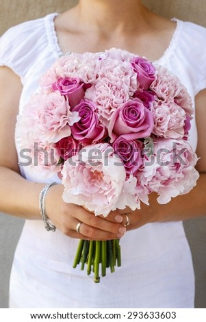 Bride holding bouquet with pink peonies and roses