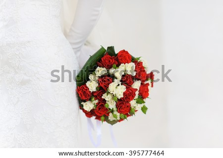 Bride  holding bridal bouquet close up. white and red roses. White background. bride in white gloves - stock photo