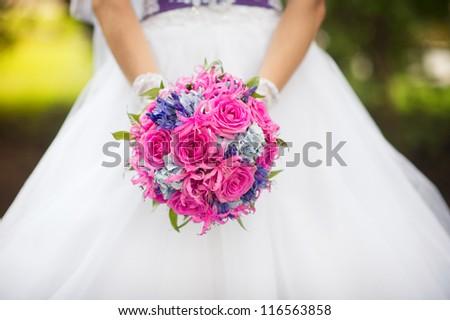 Bride holding bright wedding bouquet - stock photo