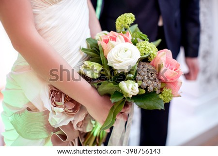 bride holding bright wedding bouquet with roses