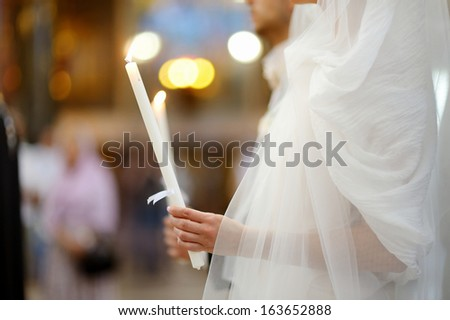 Bride holding candle in an orthodox wedding ceremony - stock photo