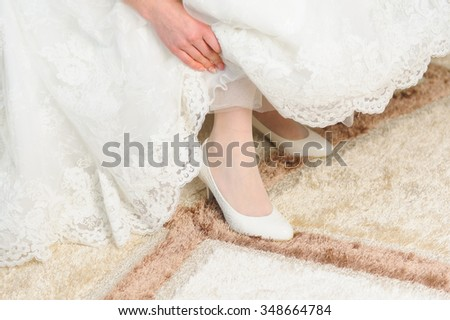 bride holding dress to show her shoes - stock photo