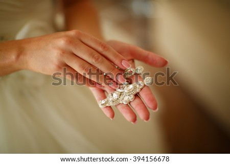 bride holding earrings