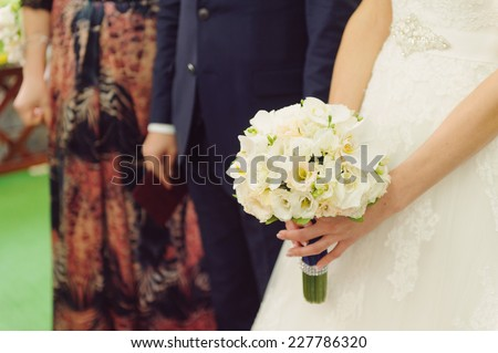 bride holding flowers at ceremony