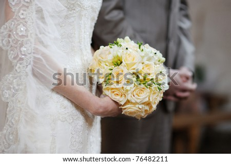 Bride holding flowers during the wedding ceremony - stock photo