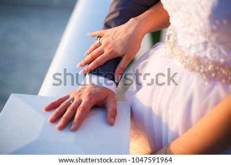 Bride holding grooms hand at sunset time
