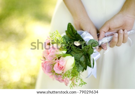 Bride holding her bouquet behind her back - stock photo