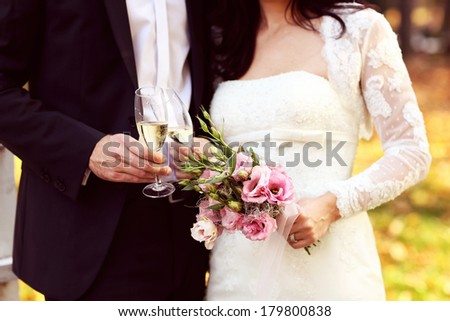 Bride holding her wedding bouquet and groom holding glass of champagne