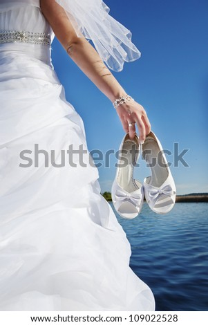 bride holding her wedding shoes on a blue background