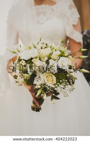 Bride holding her white and green wedding bouquet