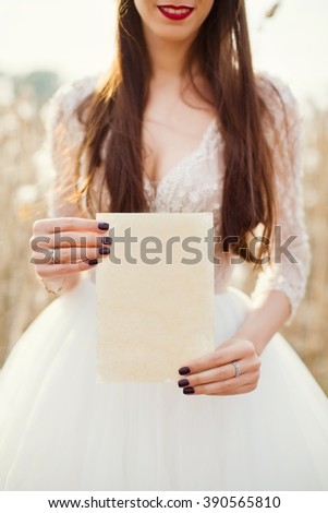 bride holding old textured paper  - stock photo