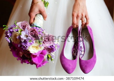Bride holding shoes and colorful bouquet - stock photo