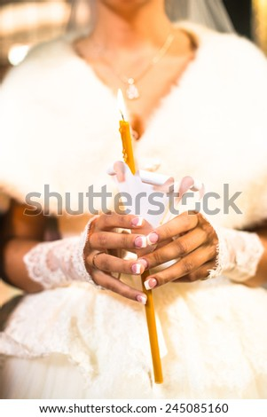 Bride holding the candle during the wedding ceremony in orthodox church. Close up. - stock photo