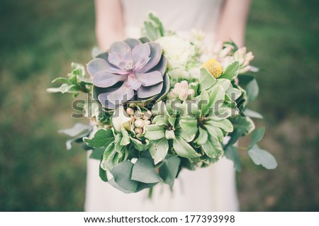 Bride holding the wedding bouquet, with succulent flowers, close-up - stock photo
