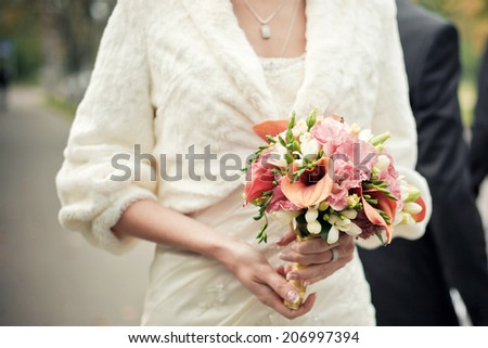 Bride holding wedding bouquet from orange calla lilies and freesia. Selective focus (on a bouquet). - stock photo